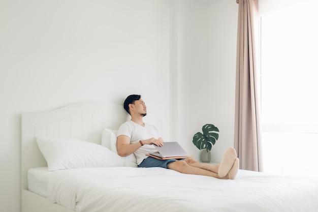 Homem deitado na cama trabalha em seu laptop no aconchegante quarto branco.