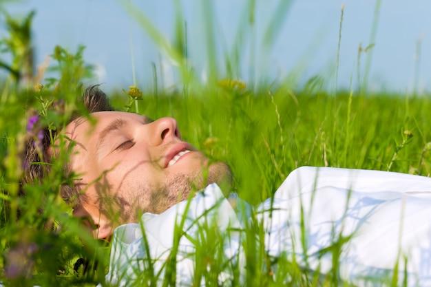 Homem deitado na grama sonhando acordado