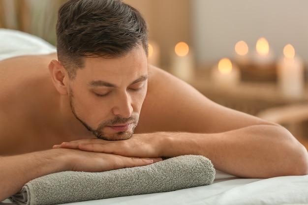 Homem deitado na mesa de massagem em salão de spa