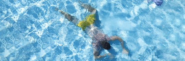 Homem deitado no fundo da piscina, close-up
