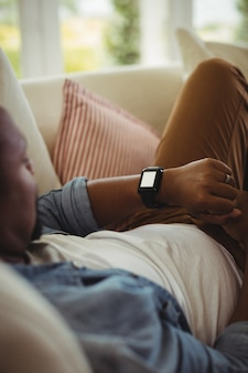 Homem deitado no sofá e verificando seu smartwatch