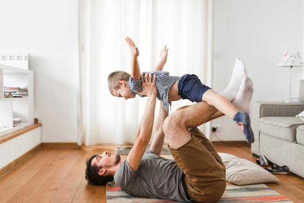 Homem deitado no tapete, brincando com seu filho em casa