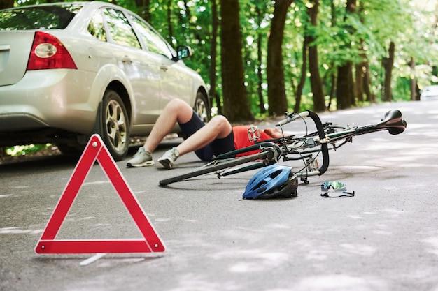 Homem deitado. vítima no asfalto. bicicleta e acidente de carro prateado na estrada na floresta durante o dia