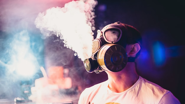 Homem deixa nuvens de cachimbo de água fumar em uma máscara de gás