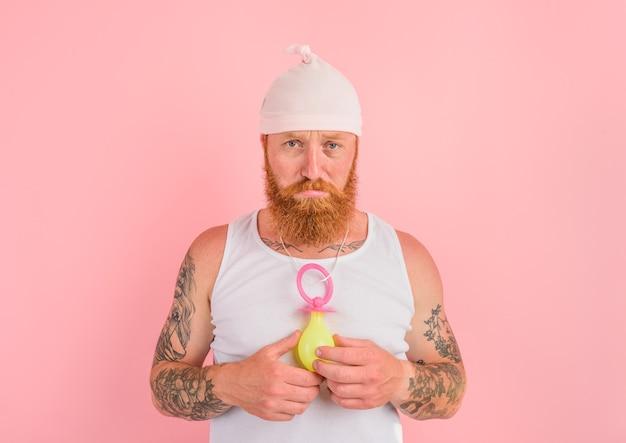 Homem delirante com barba e tatuagens age como um pequeno recém-nascido