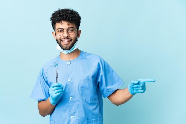 Homem dentista marroquino segurando ferramentas isoladas, apontando o dedo para o lado e apresentando um produto