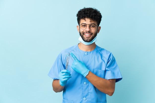 Homem dentista marroquino segurando ferramentas isoladas em azul apontando para o lado para apresentar um produto