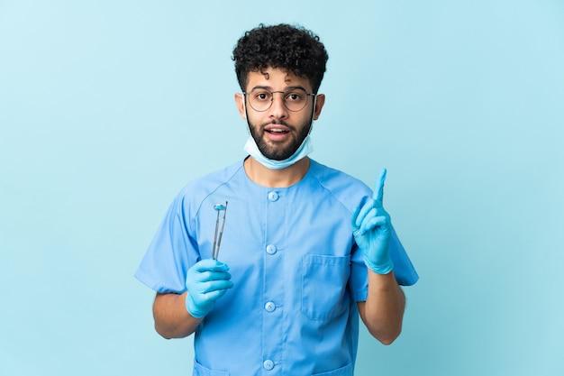 Homem dentista marroquino segurando ferramentas isoladas em azul com a intenção de descobrir a solução enquanto levanta um dedo