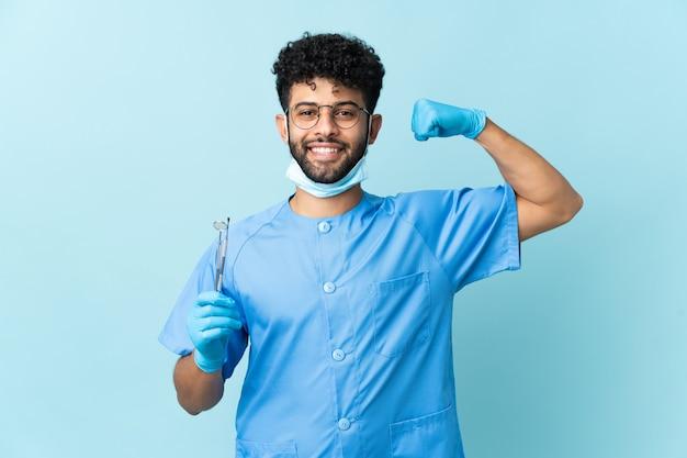 Homem dentista marroquino segurando ferramentas isoladas em azul, fazendo gestos fortes