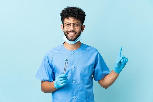 Homem dentista marroquino segurando ferramentas isoladas em azul, mostrando e levantando um dedo em sinal dos melhores