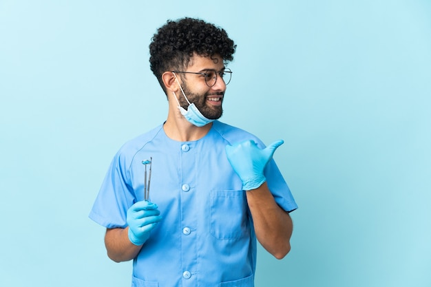 Homem dentista marroquino segurando ferramentas isoladas em um fundo azul apontando para o lado para apresentar um produto