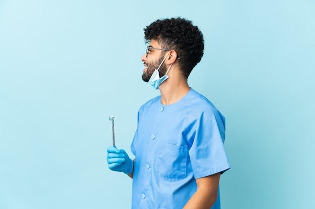 Homem dentista marroquino segurando ferramentas isoladas rindo em posição lateral