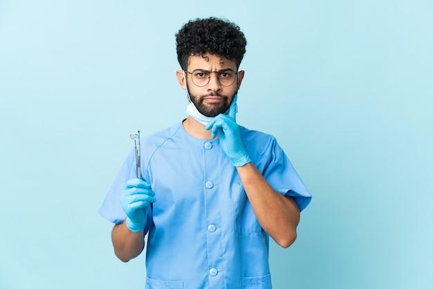 Homem dentista marroquino segurando ferramentas isoladas, tendo dúvidas e pensando
