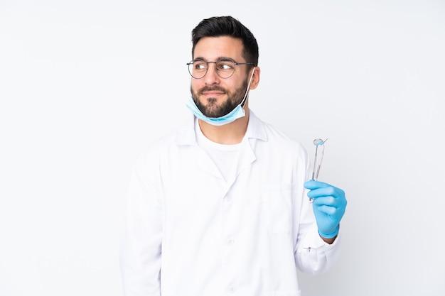 Homem dentista segurando ferramentas isoladas em branco, em pé e olhando para o lado