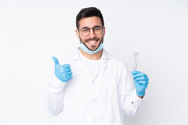 Homem dentista segurando ferramentas na parede branca, dando um polegar para cima gesto