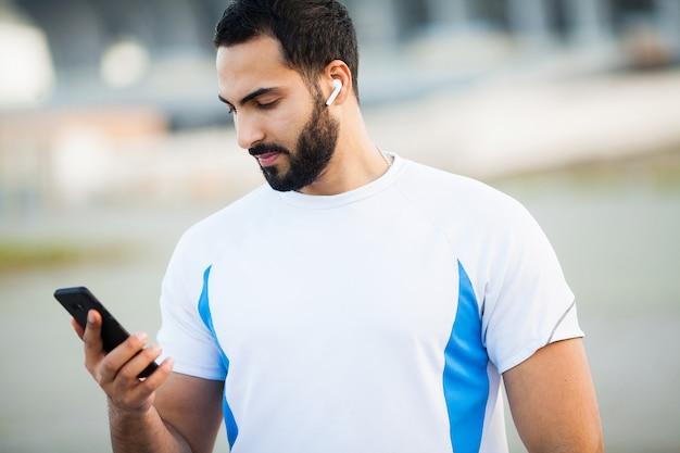 Homem depois de malhar no parque da cidade e usando seu telefone celular