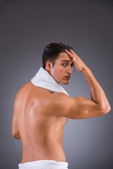 Homem depois de tomar banho no fundo escuro