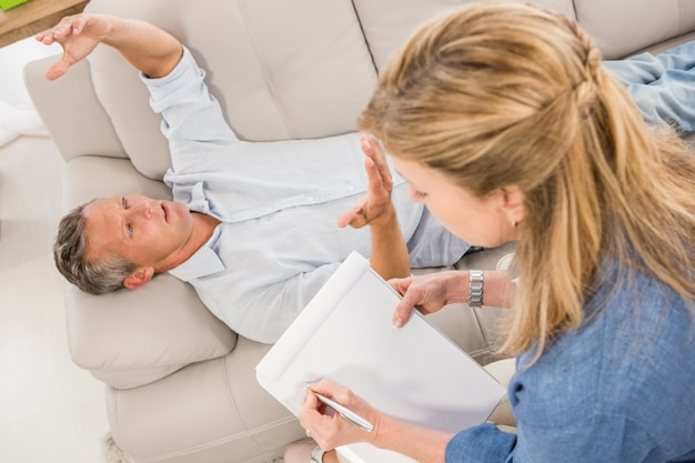 Homem deprimido deitado no sofá e conversando com o terapeuta