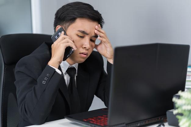 Homem deprimido no terno falando no smartphone