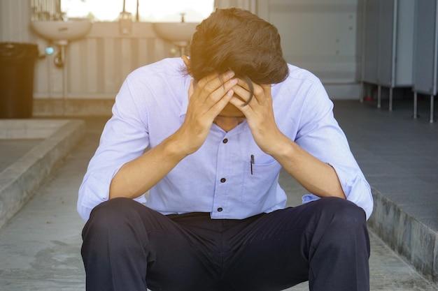 Homem deprimido, segurando a testa com as duas mãos, sentado na escada do vaso sanitário