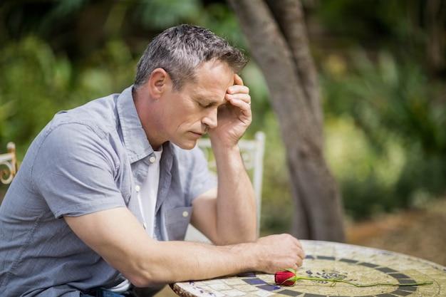 Homem deprimido, tocando sua testa, sentado do lado de fora