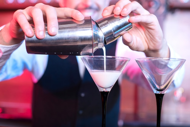 Homem derrama um coquetel em copos no bar.