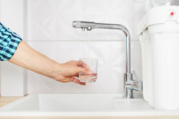 Homem derramando água da torneira com filtro de osmose na cozinha.