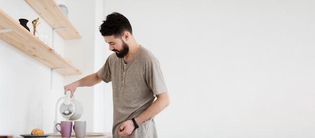 Homem derramando água quente em canecas