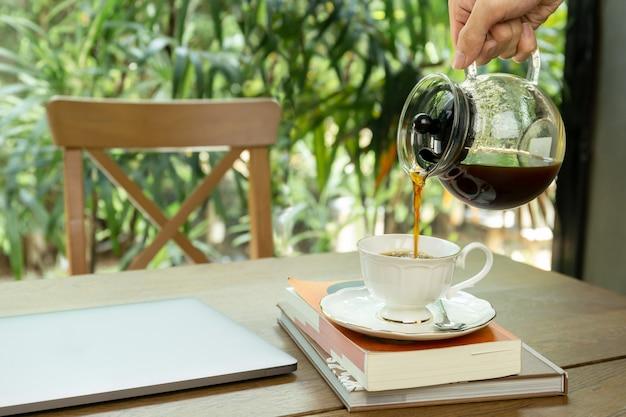 Homem derramando café em uma xícara com laptop em cima da mesa.