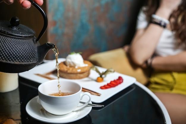 Homem derramando chá com torta de maçã sorvete de menta morango vista lateral