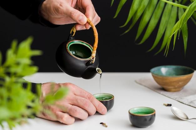 Homem derramando chá na xícara de chá