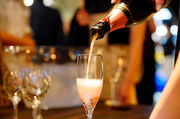 Homem derramando champanhe em um copo