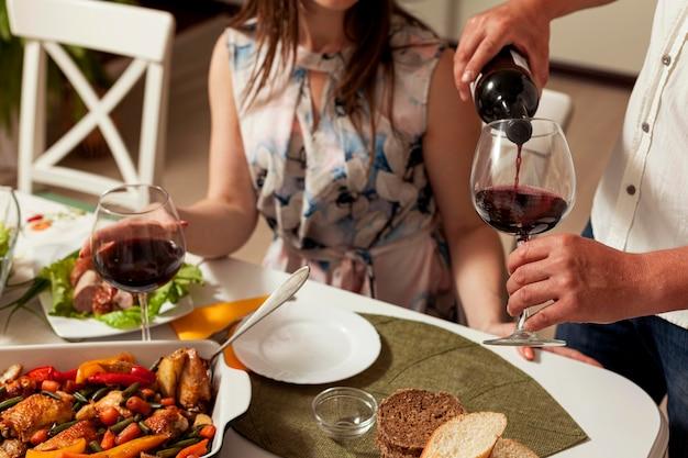 Homem derramando vinho em vidro na mesa de jantar