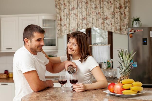 Homem derramando vinho para sua esposa