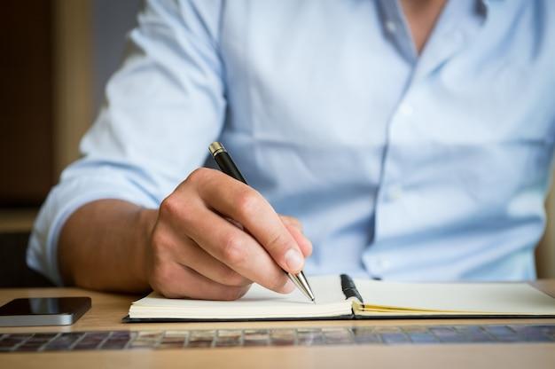 Homem derrubando nota no diário
