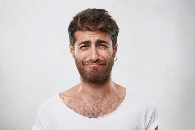 Homem desanimado com penteado e barba franzindo a testa, lamentando o que fez. homem entristecido em uma camiseta branca. pessoas, moda, estilo de vida, conceito de emoções