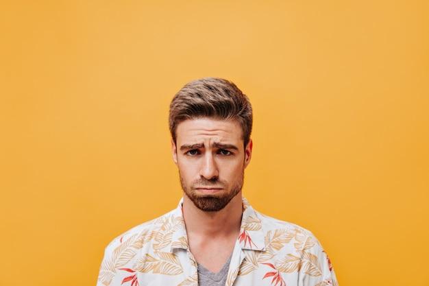 Homem desapontado com um penteado elegante e barba em uma roupa branca da moda, olhando para a câmera em uma parede laranja isolada