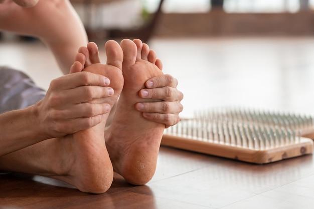 Homem descalço sentado no chão de madeira com almofadas de terapia de ioga com unhas metálicas próximas e segurando os pés nas mãos durante um dos exercícios