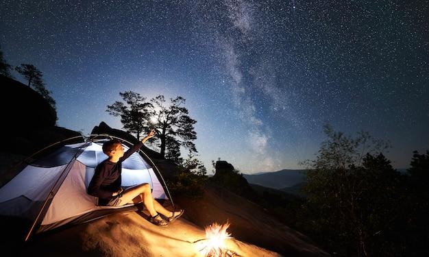 Homem descansando ao lado do acampamento, fogueira e barraca para turistas à noite