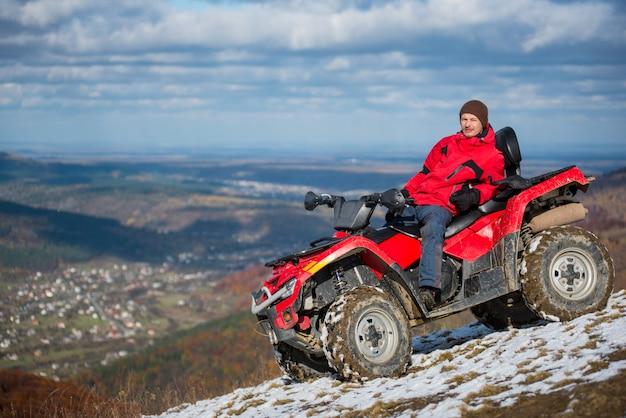 Homem descansando em uma bicicleta atv vermelha no topo de uma montanha de neve