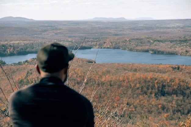 Homem descansando em uma montanha com uma bela vista do rio e da planície