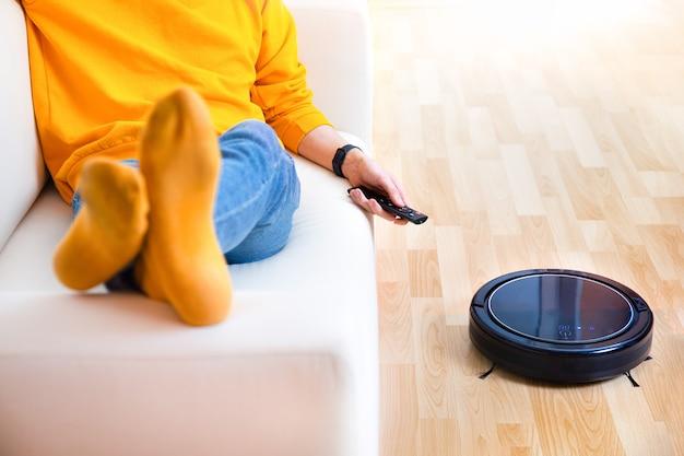 Homem descansando enquanto aspirador de pó robótico fazendo tarefas domésticas, trabalho limpo em casa.