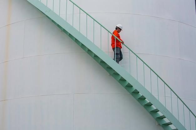 Homem descendo a escada inspeção de óleo do tanque de armazenamento visual