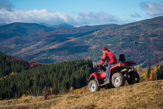 Homem descendo em um atv a estrada montanhosa
