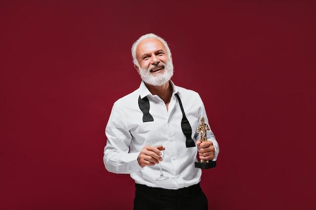 Homem descolado com camisa branca clássica segurando um vidro e uma estatueta de prêmio