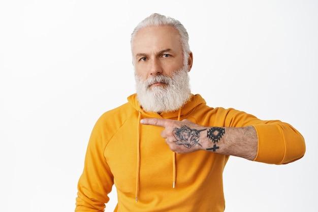 Homem descolado e hippie sênior com tatuagens apontando para a esquerda no espaço da cópia, mostrando anúncio, vovô com barba comprida usando um capuz elegante, recomendando clique no link, parede branca
