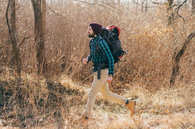 Homem descolado e moderno viajando com uma mochila na floresta de outono, vestindo uma camisa xadrez e um chapéu