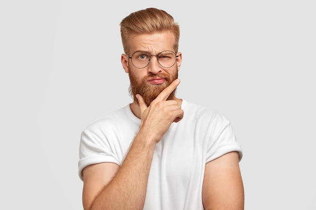 Homem descolado moderno com cabelo ruivo espesso, segura o queixo, pisca com os olhos, tem penteado da moda