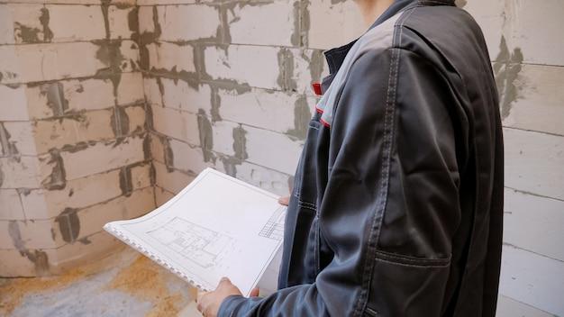 Homem desconhecido de uniforme, trabalhando no local da nova casa de pé na sala vazia com planos de papel.