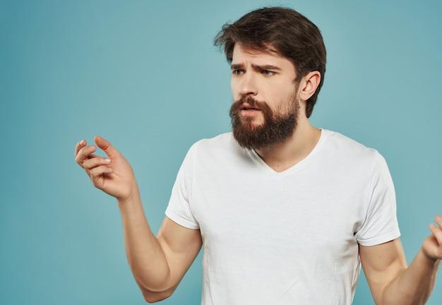Homem descontente em camiseta branca raiva grito emoção fundo azul